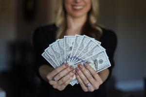 お金を持った女の人の画像